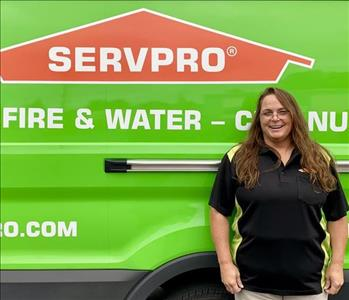 female employee standing next to a SERVPRO vehicle
