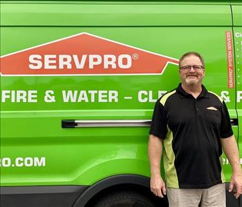 male employee  standing next to a SERVPRO vehicle