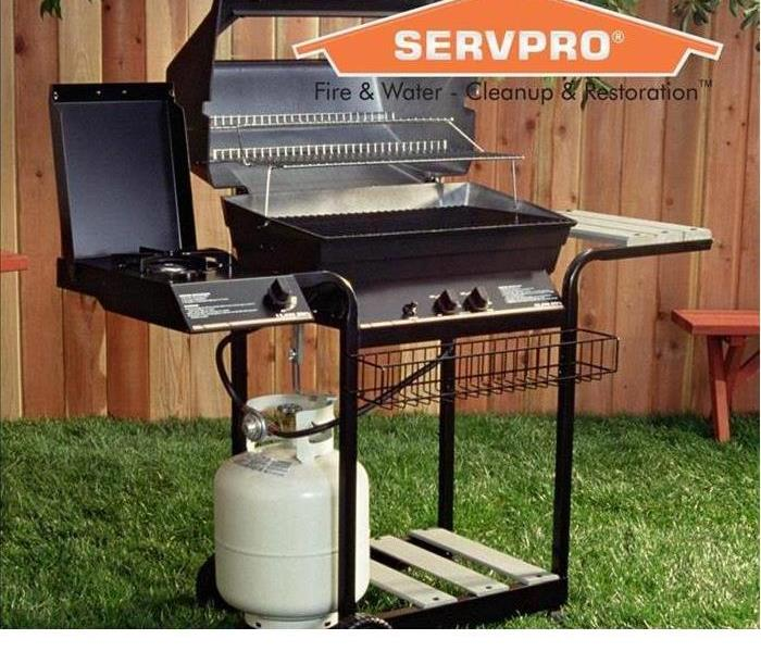 BBQ in grass with SERVPRO log